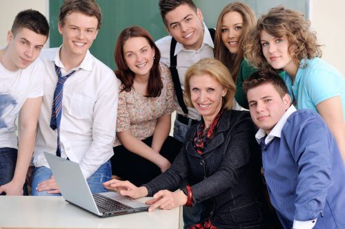 Teacher with laptop posing with students